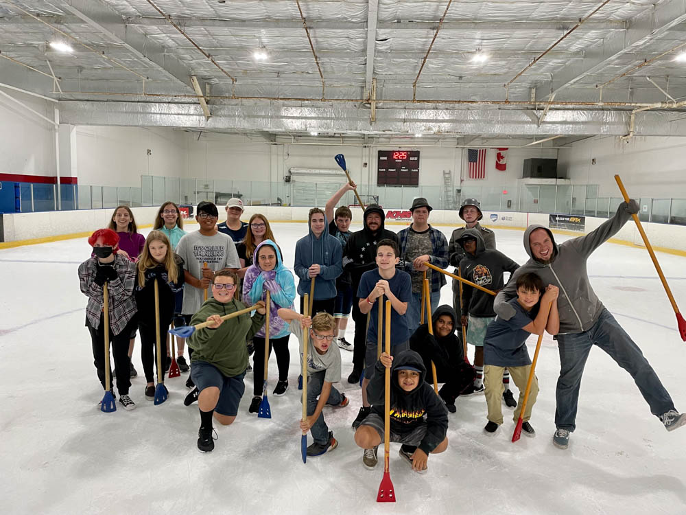 Group of teens and adults gathered on an ice rink after a game of broom ball