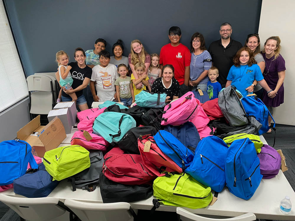 Parents and Kids with large pile of filled backpacks