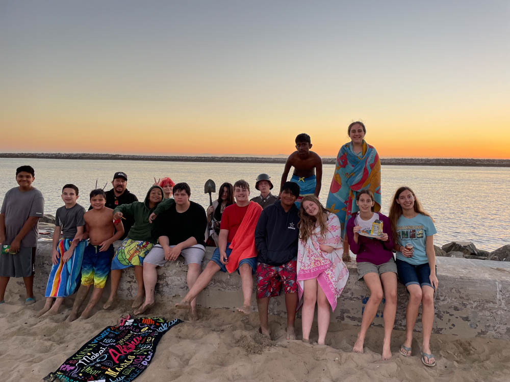 group of youth near ocean jetty at sunset