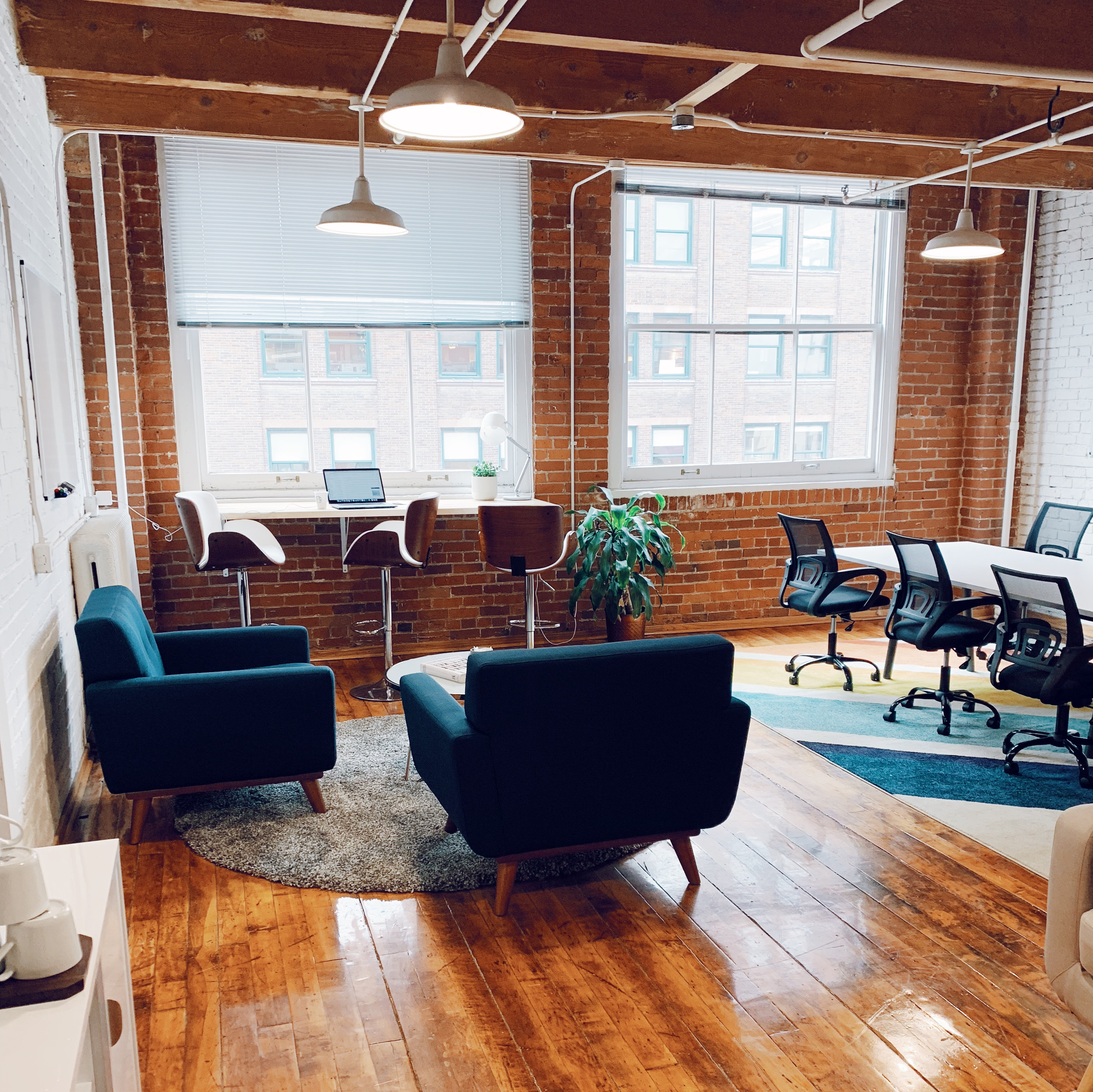 Beautiful mid-century office space with blue chairs and hardwood floors
