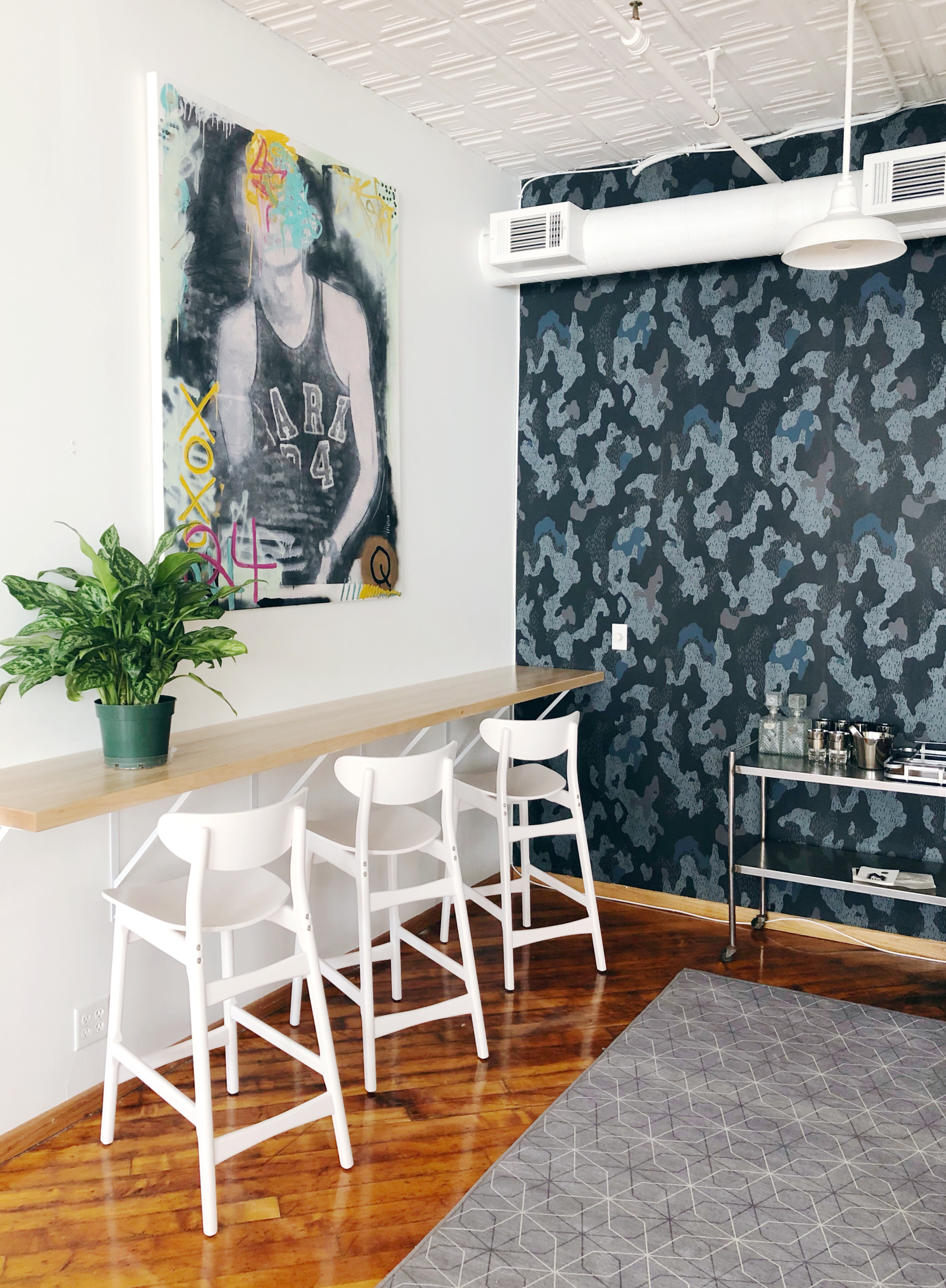 Office nook with interesting wallpaper, custom painting and bar cart