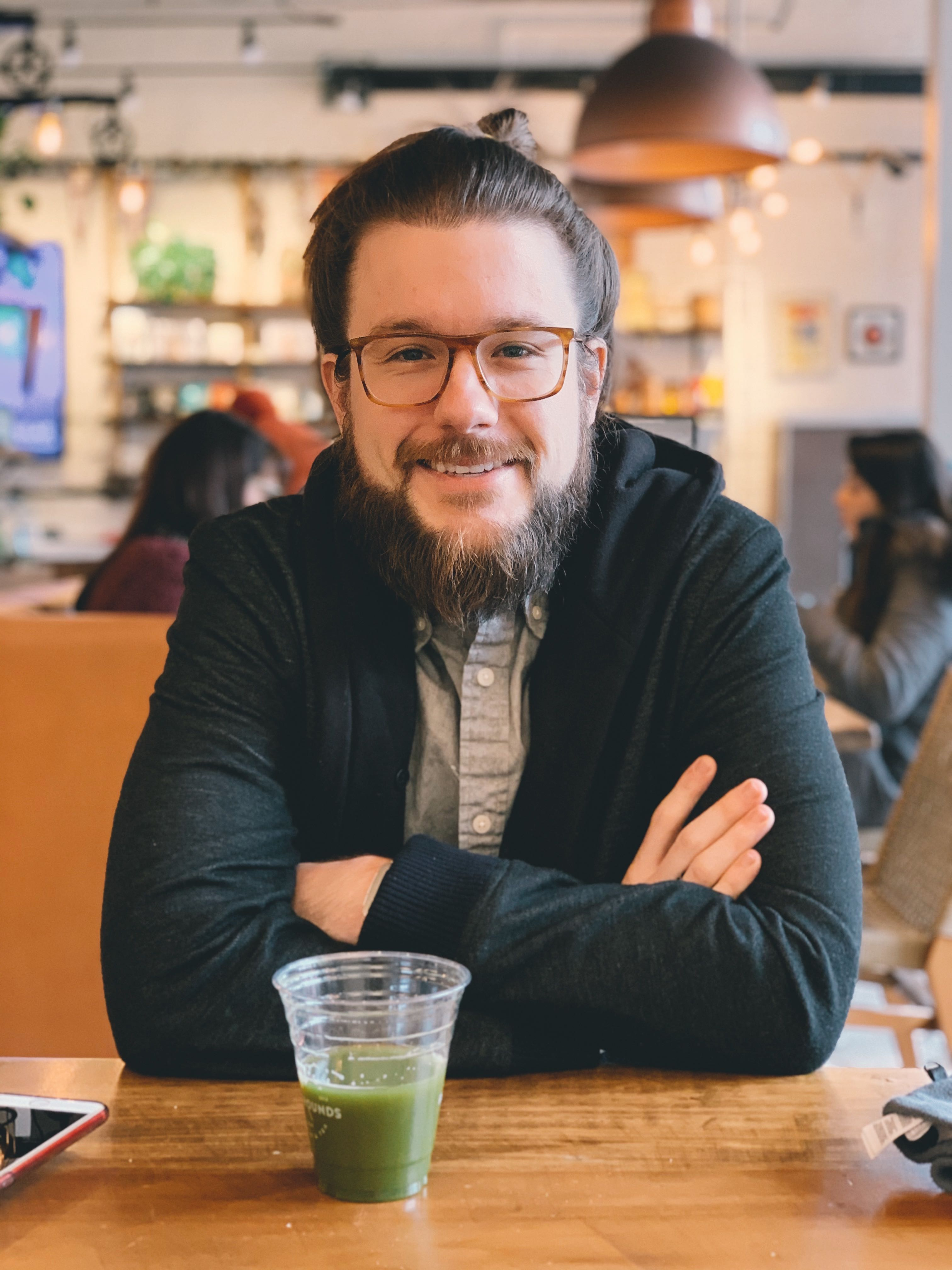 Charming photograph of Range employee, Noah Jeffrey having coffee