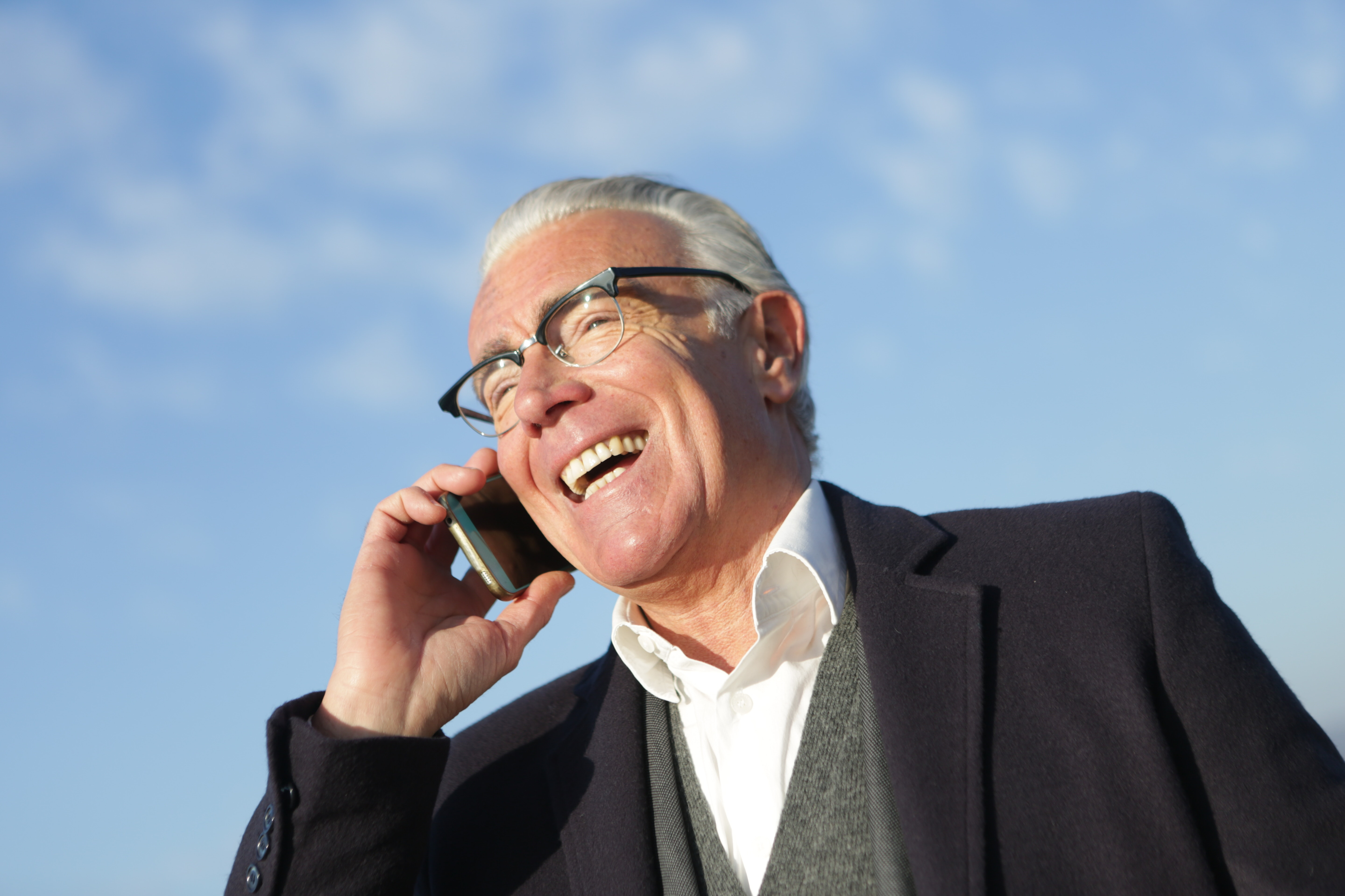business man talking on the phone and smiling with blue sky in the background