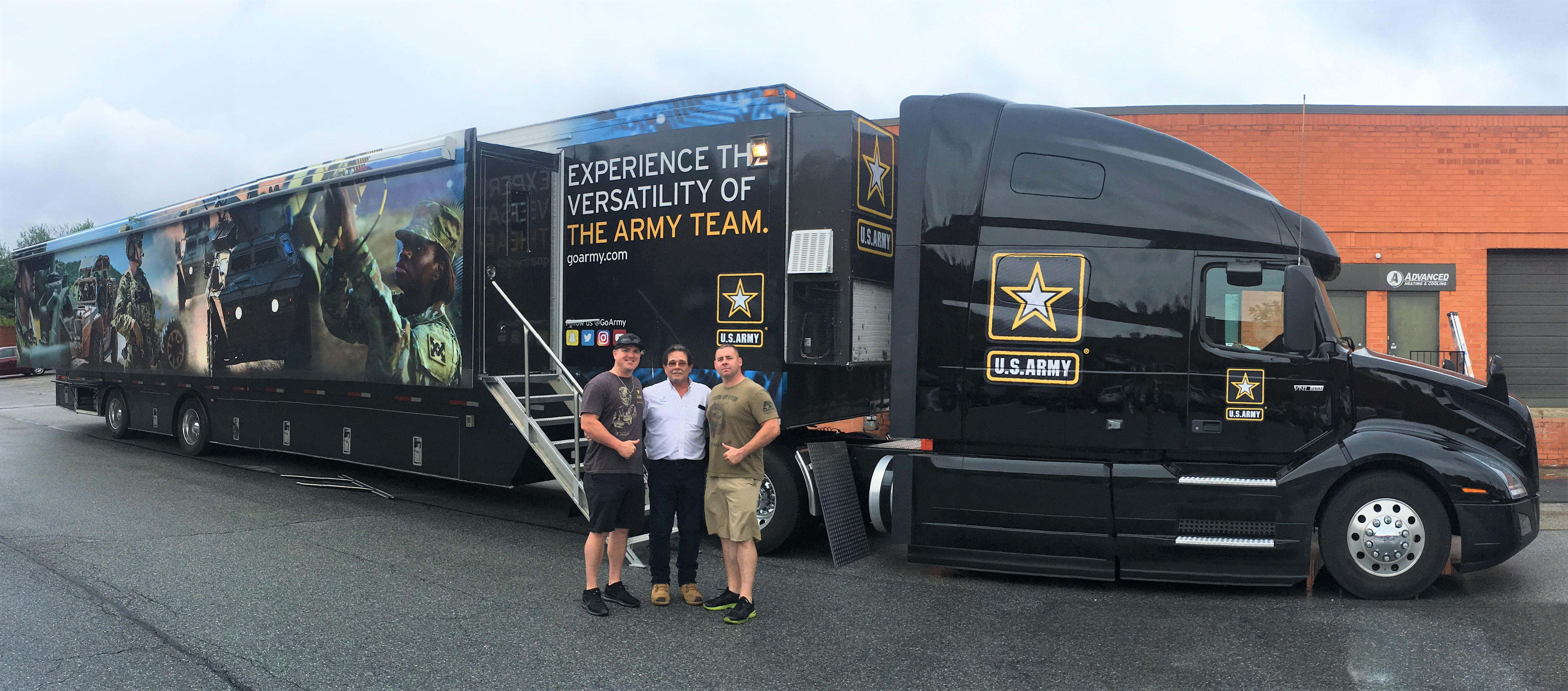 3 men standing and smiling in front of a truck that is advertising for the U.S. Army