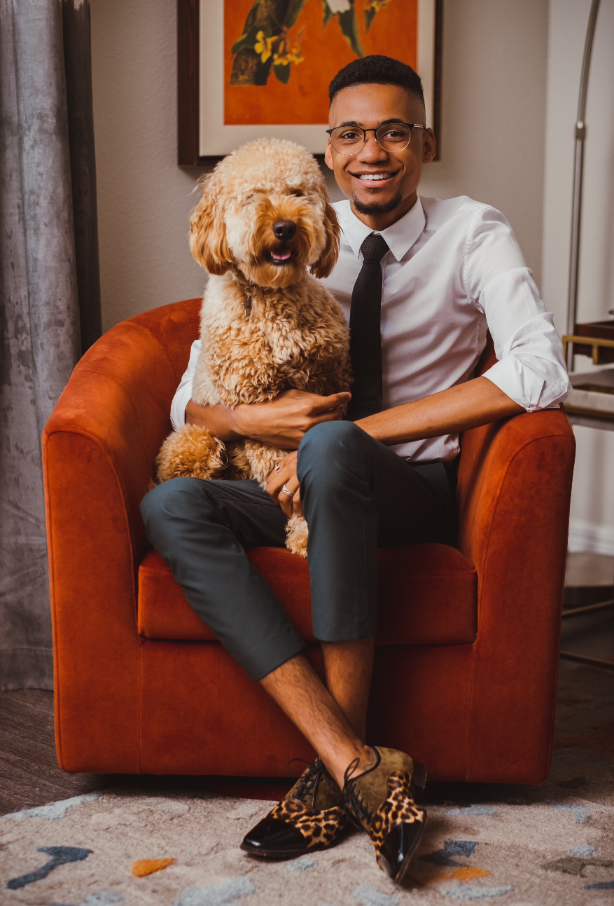Owner of ZB Home Company sitting in an orange chair with his dog.