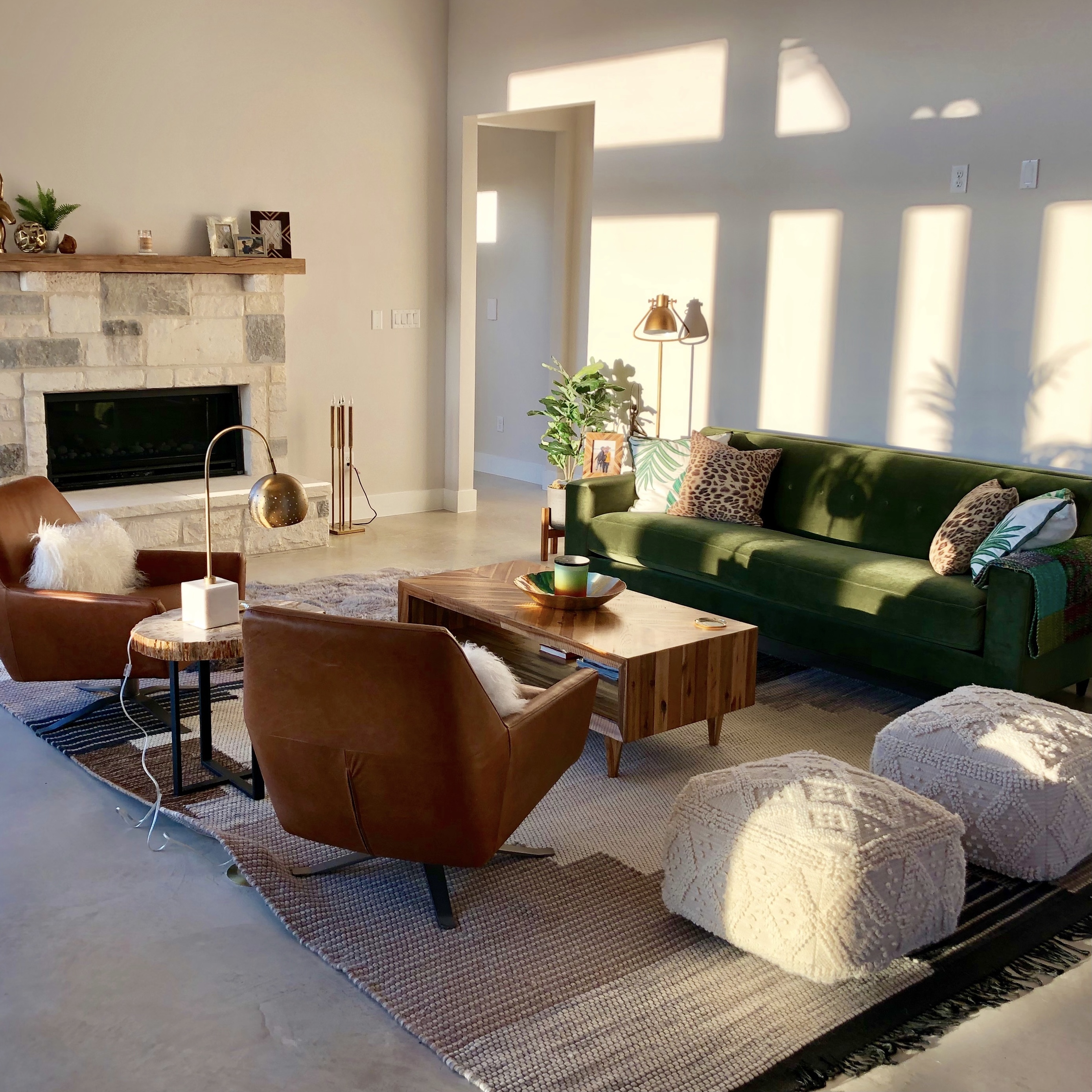 Living room with sunlight coming in through window hitting wall on right hand side. Chimney on the left hand side with white and grey stone and wood decor on top. Green sofa and brown chair accents. Wood coffee table in the middle with a grey carpet. Plant next to green sofa.