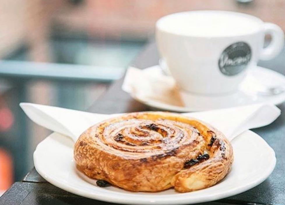 Sweet roll wits a white cup of freshly brewed coffee