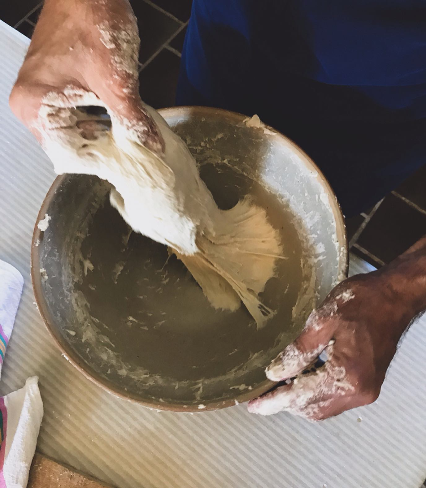 Another closeup of a man making a dough in a metal bowl