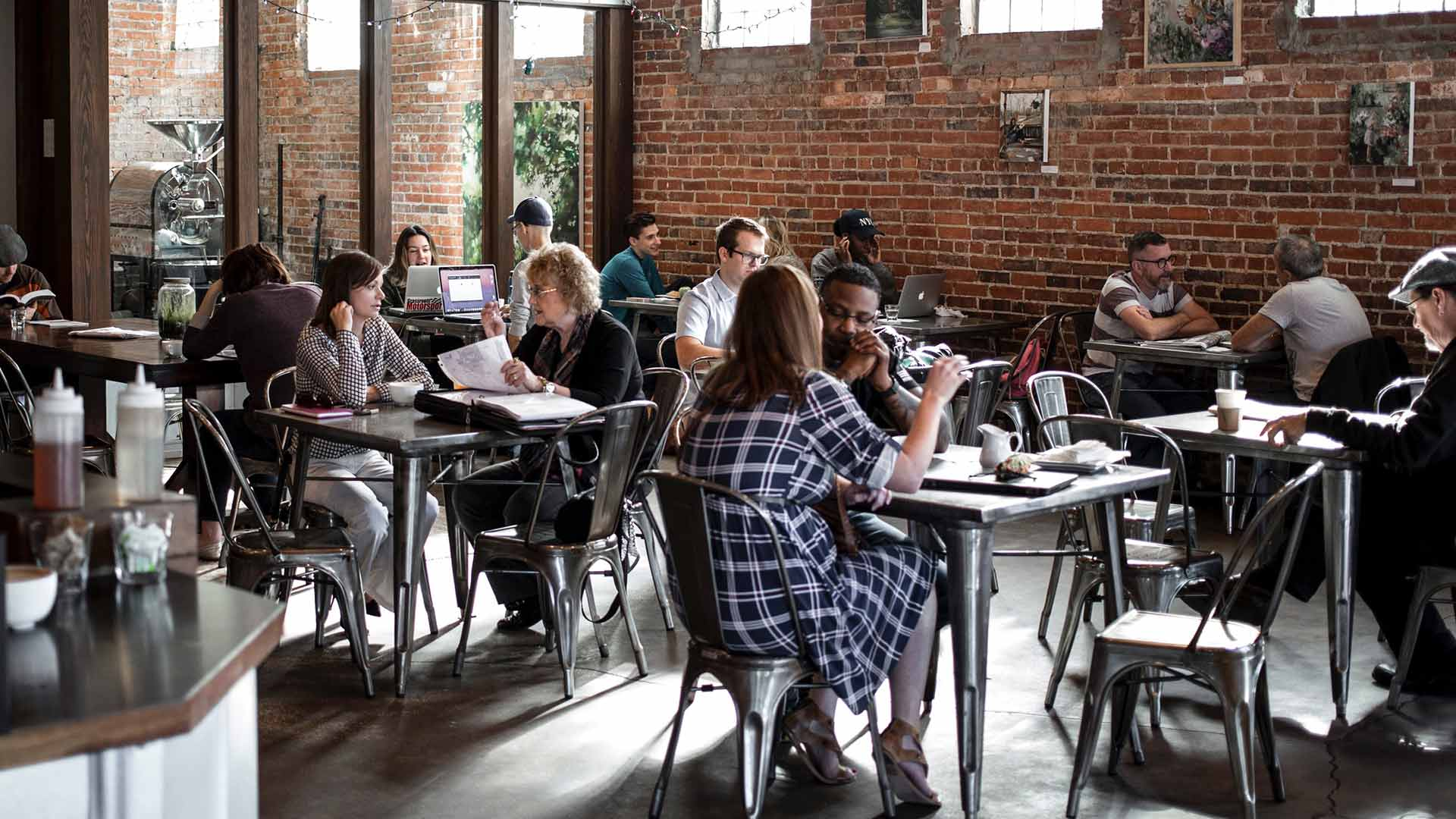 Groups of diverse people sitting at tables in a large warehouse coffee shop working and discussing business with one another.