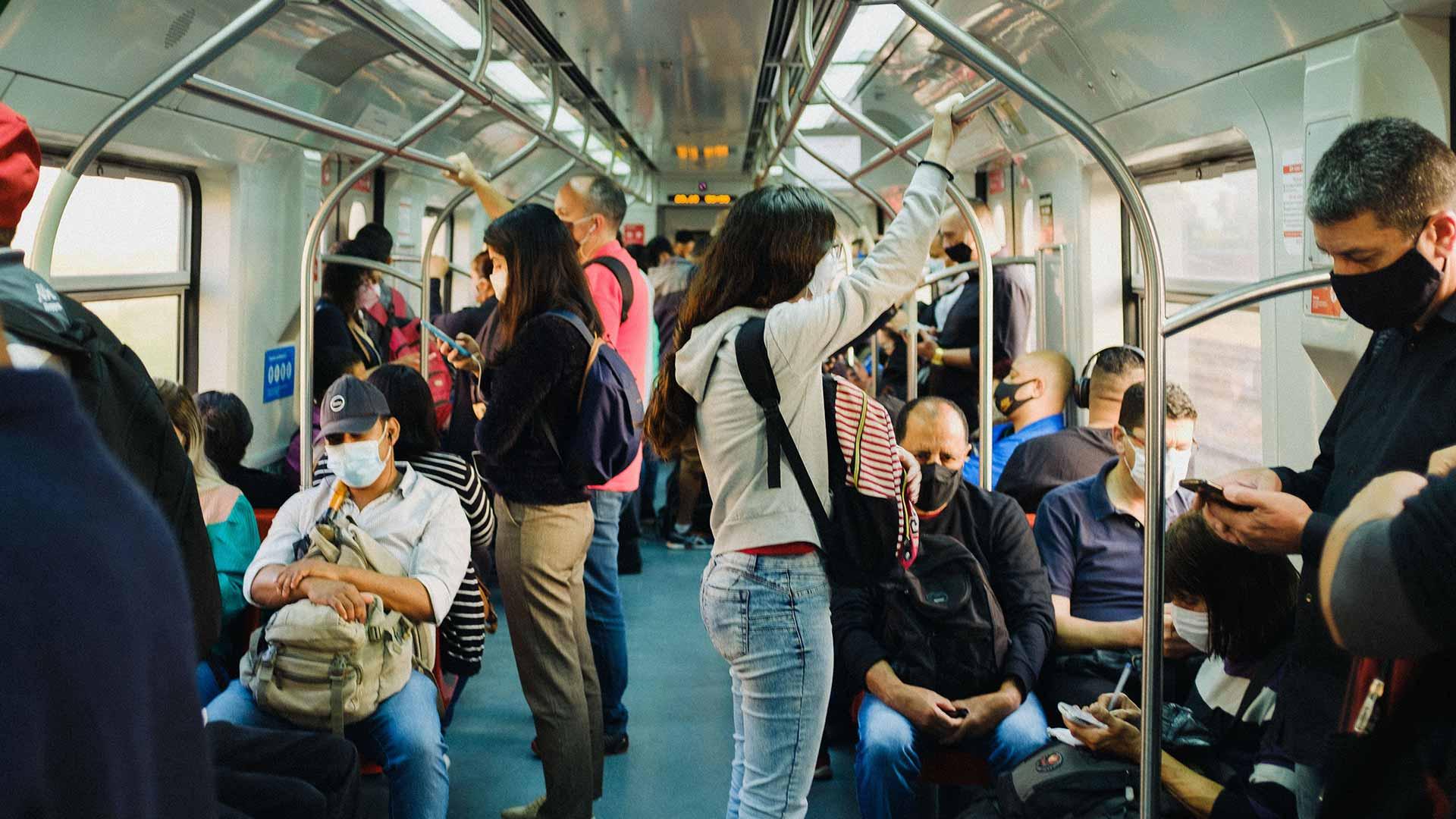 A dozen passengers aboard a train in a city.