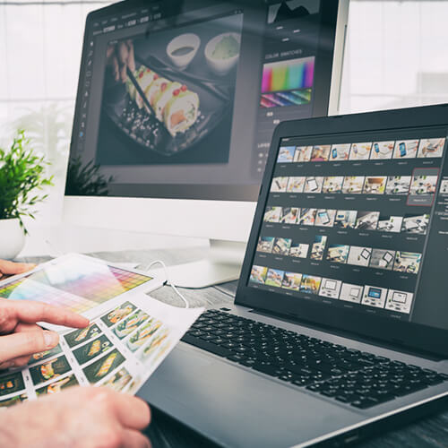 Close up of a designer editing images and video content on a computer and a laptop simultaneously