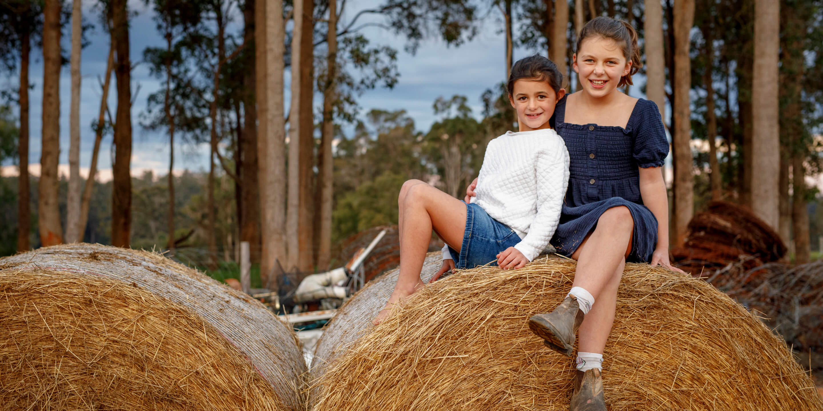 Two young girls sitting on a bail of hay on the Diamond Tree farm