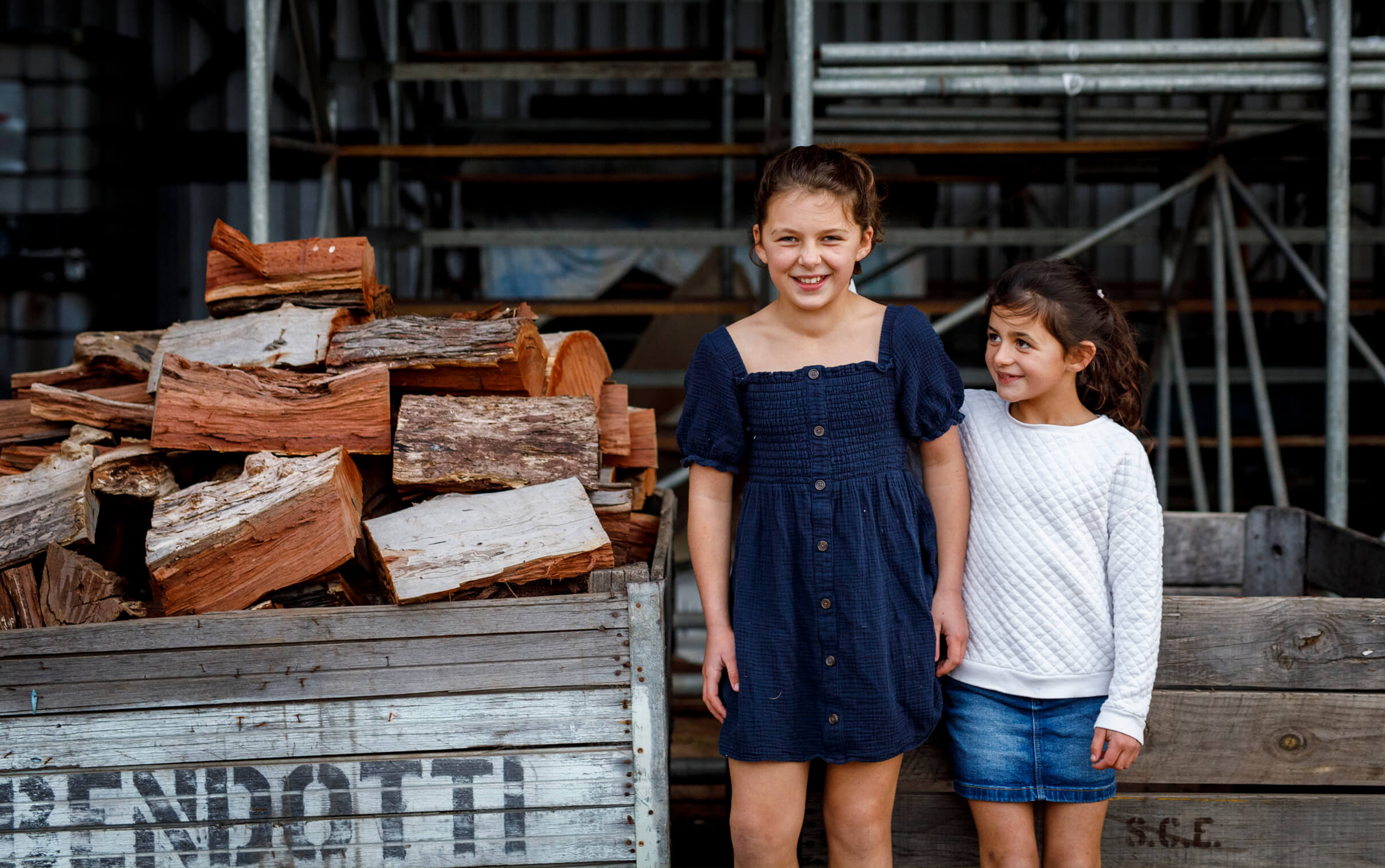 Two young girls stand beside a pile of chopped wood. The younger girl is looking up at the older girl who is laughing..