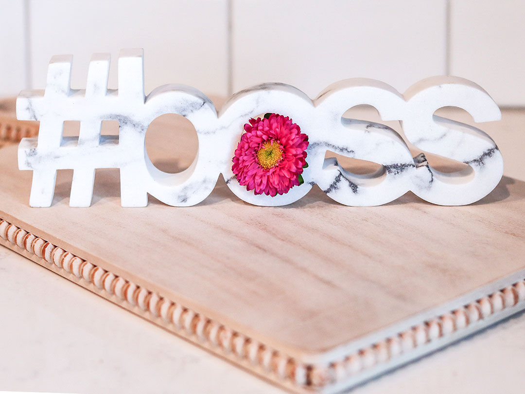 "A white and grey marble carving placed on a counter top that reads, ""#boss"" with a pink flower stuck in the counter of the ""o""."