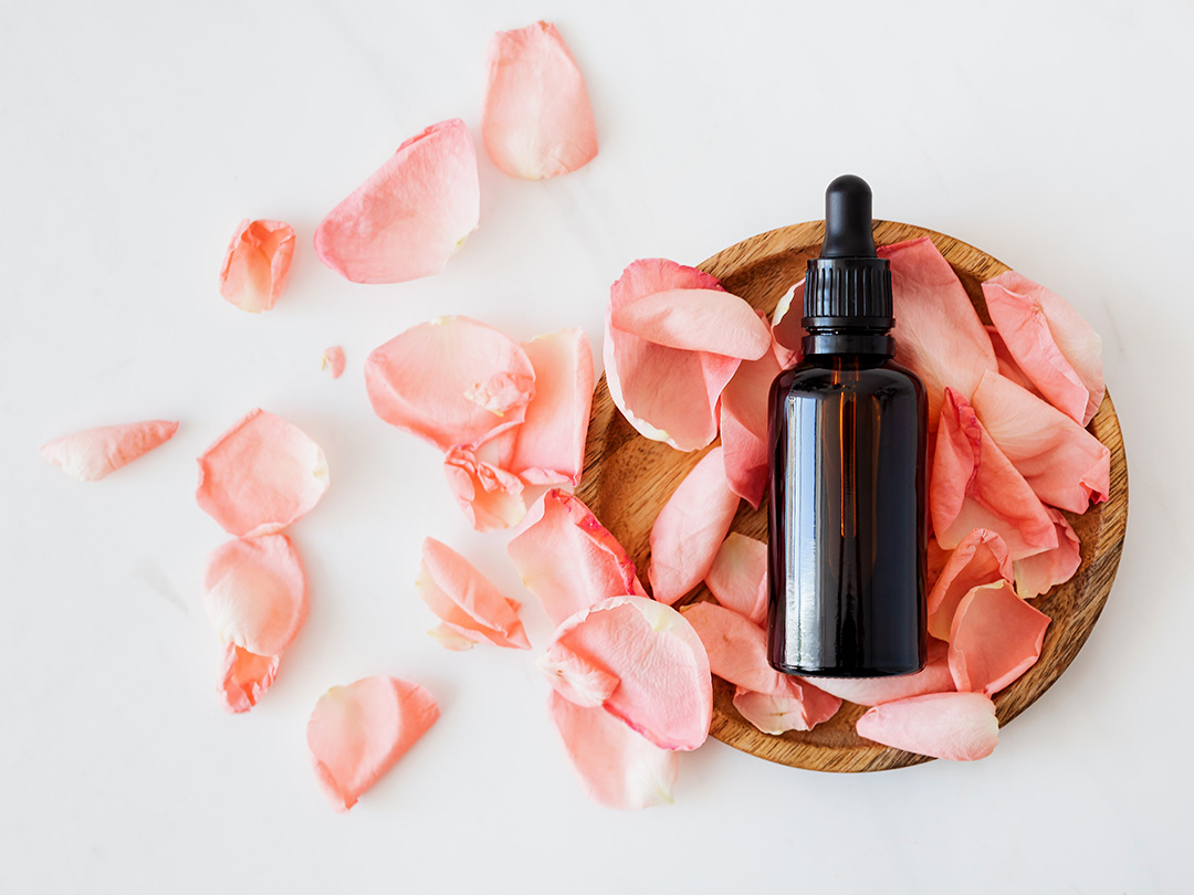 An amber glass essential oil dropper bottle surrounded by loose light pink rose petals.