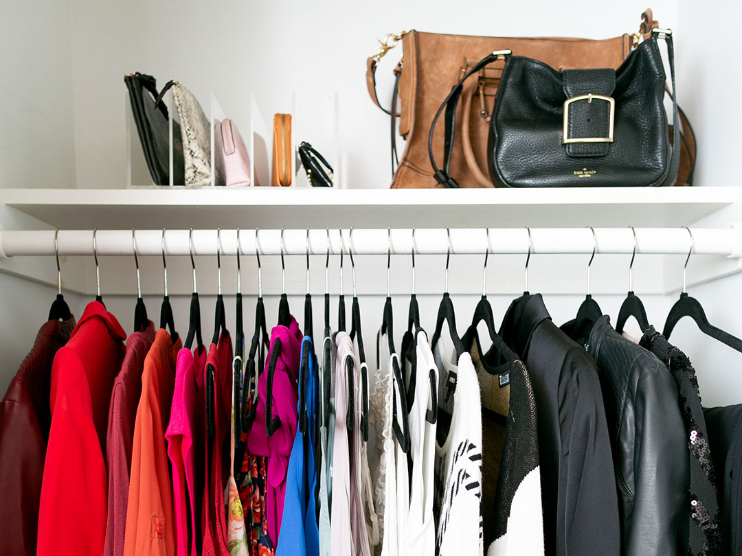 A small closet with nice dress tops organized by style and color on hangers and clutches and purses on the shelf above the hanging rod.