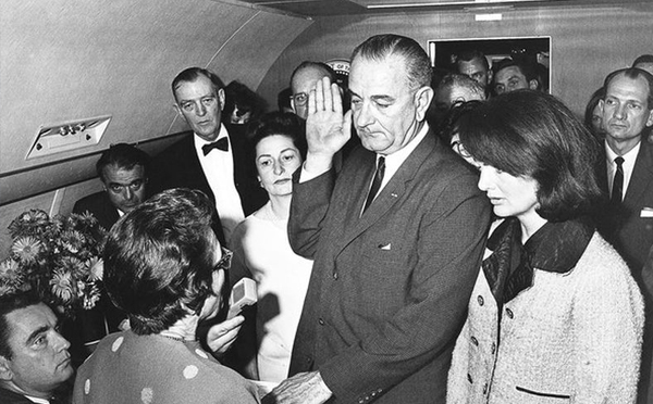 Lyndon B. Johnson takes the Oath of Office aboard Air Force One