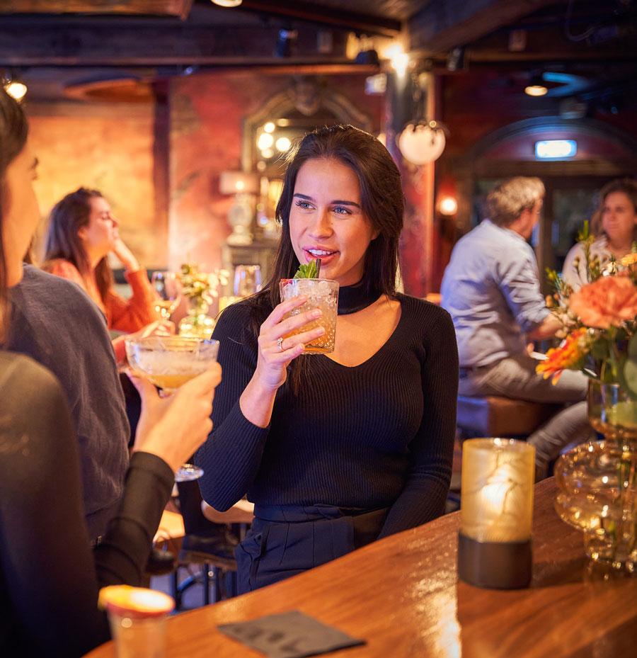 Vrouw met drankje in grand café Merlijn