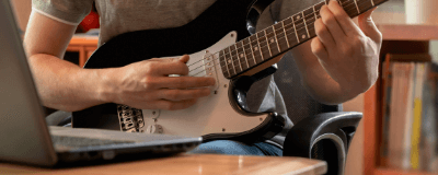 playing the guitar in front of a computer