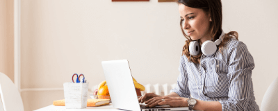 woman working on computer with headphones
