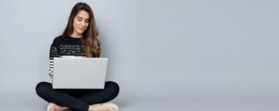 women working on computer sitting on floor