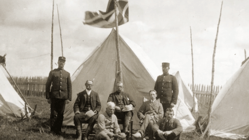 Old black and white photo of men posing for a photo in front of a teepee tent.