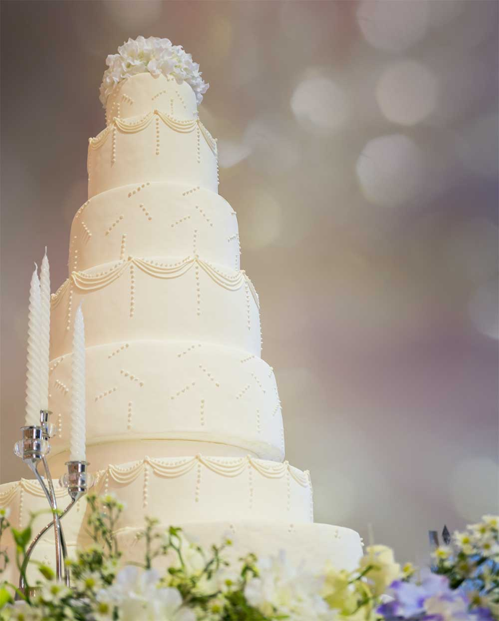 four-tier wedding cake surrounded by flowers and candles