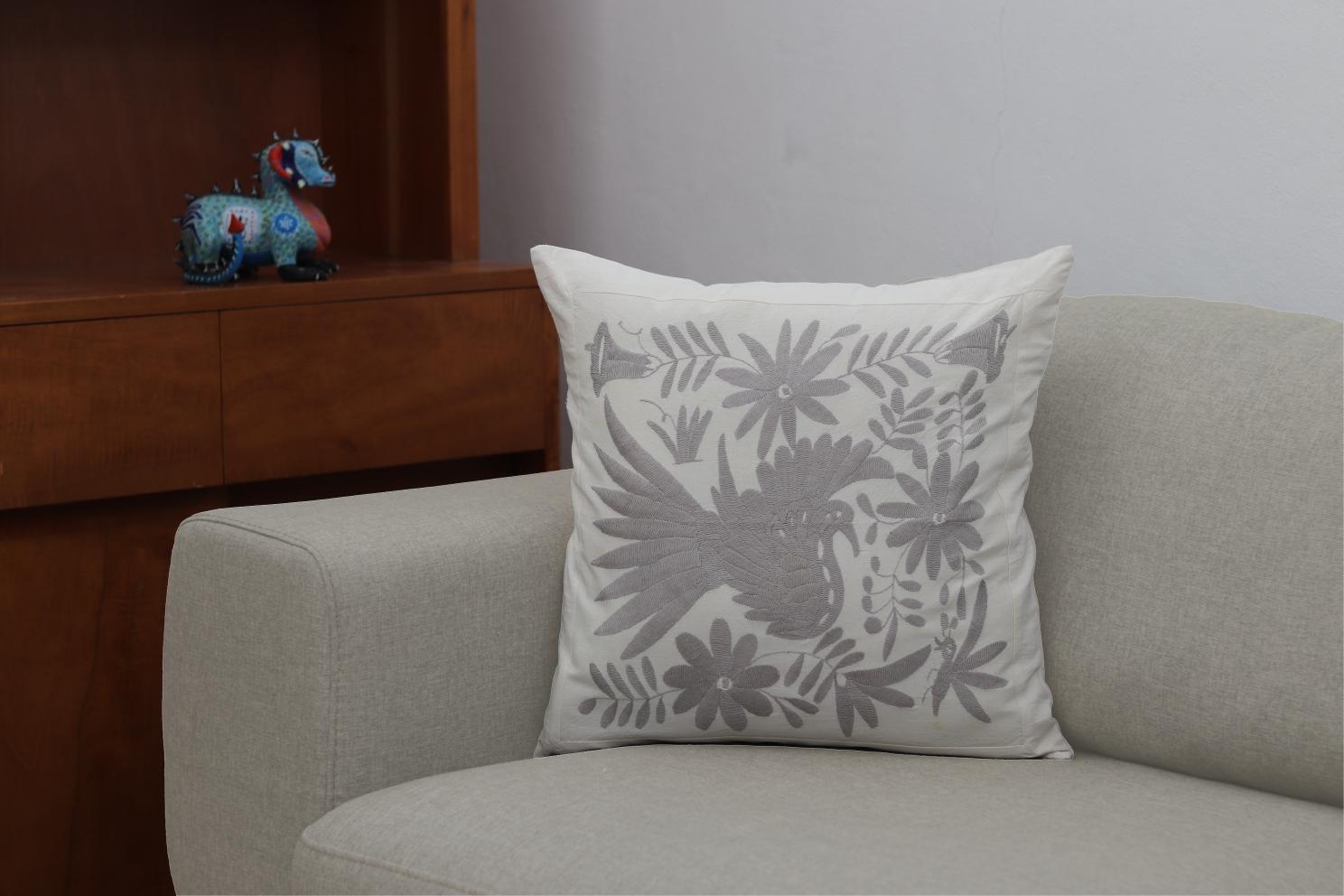 Funda de cojín cuadrada, sobre un sillón que cambia de color.