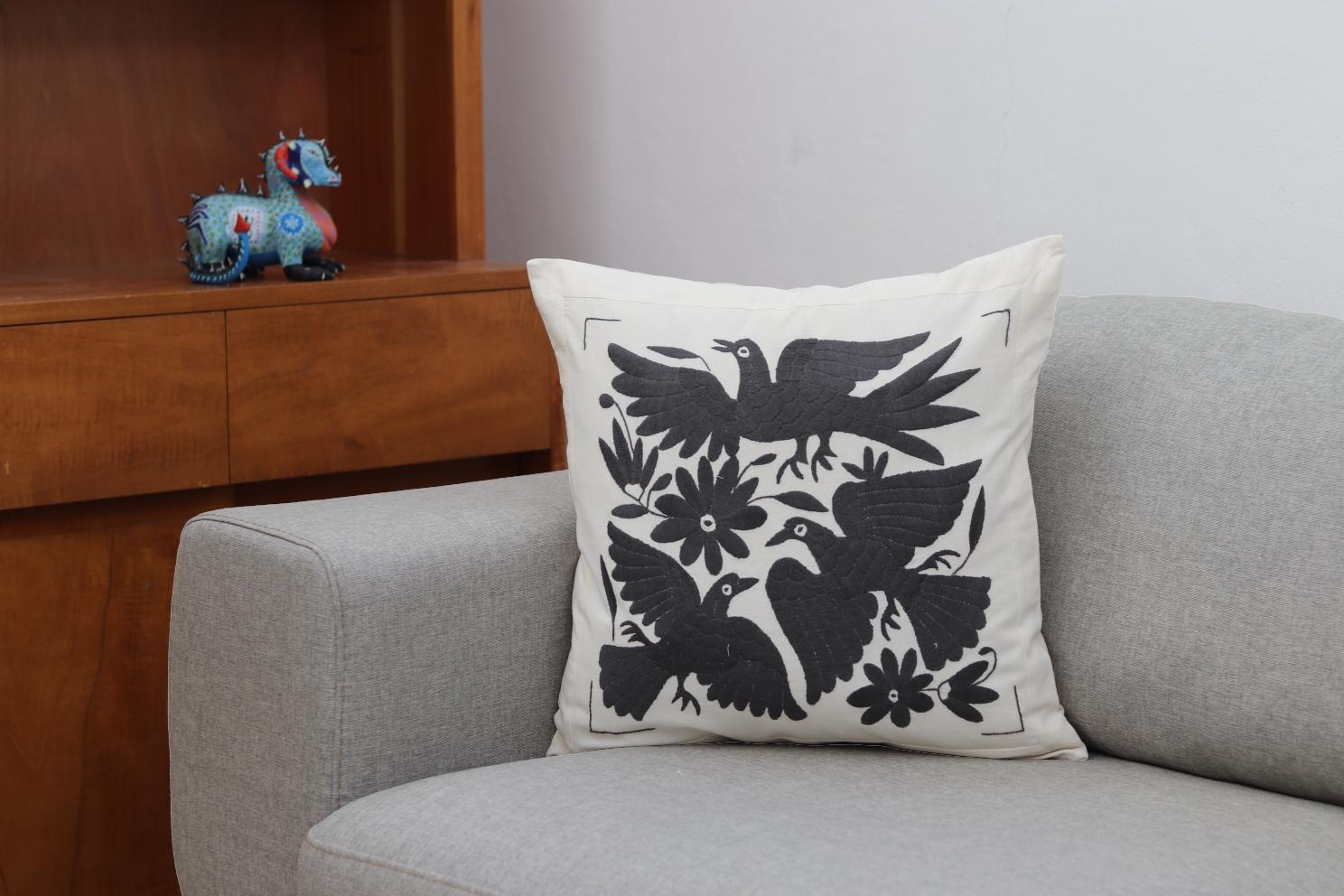 Funda de cojín colocada sobre un sillón, bordada a mano, cuadrada.