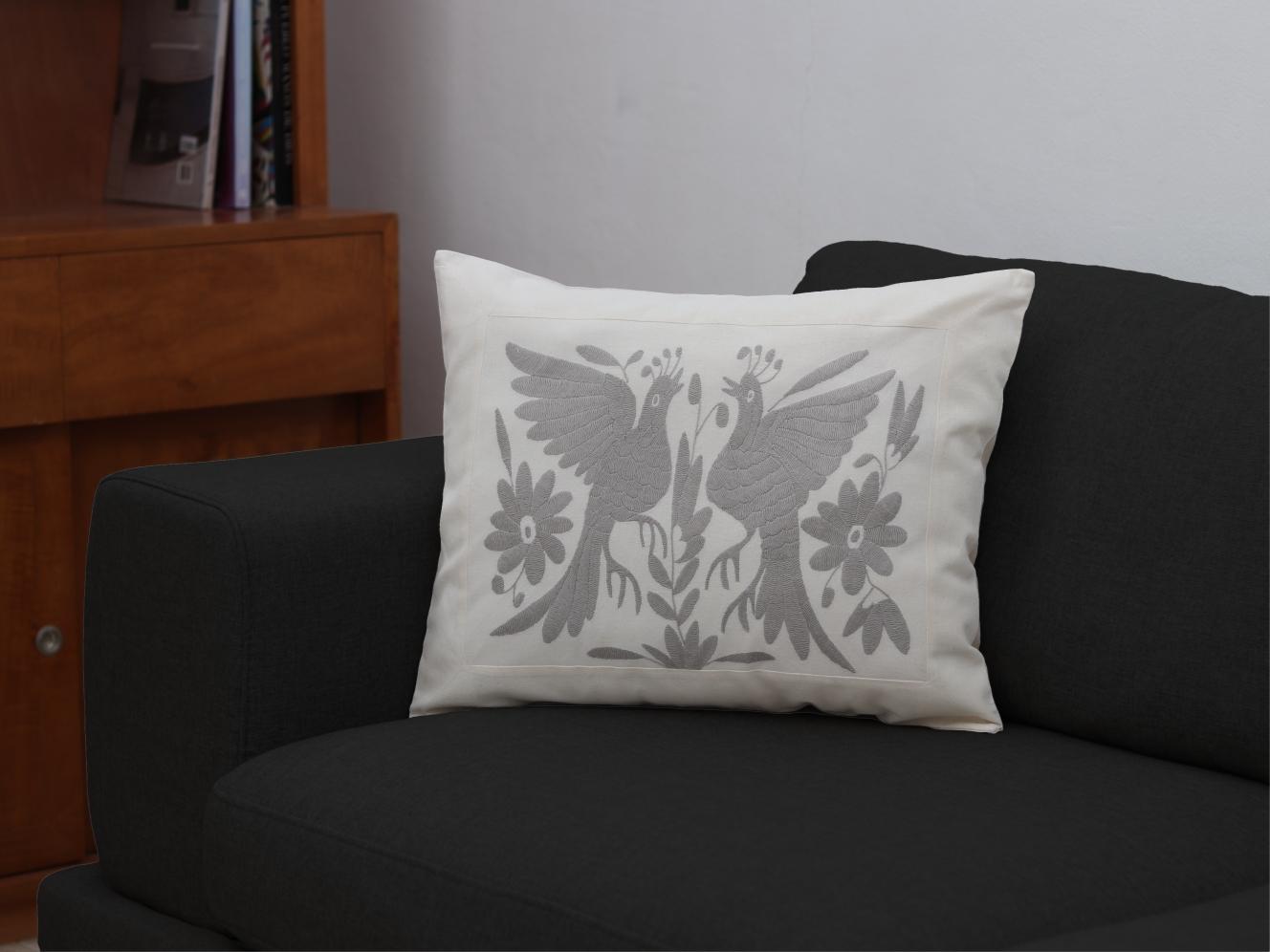 Funda de cojín rectangular, sobre un sillón que cambia de color.