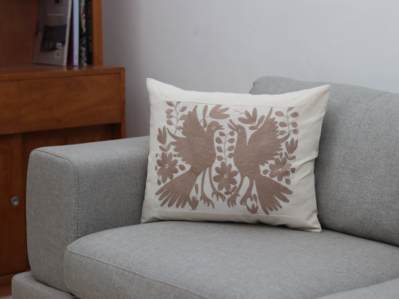 Funda de cojín colocada sobre un sillón, bordada a mano, rectangular.