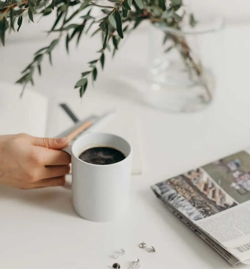 Tea and newspaper with Plants on table