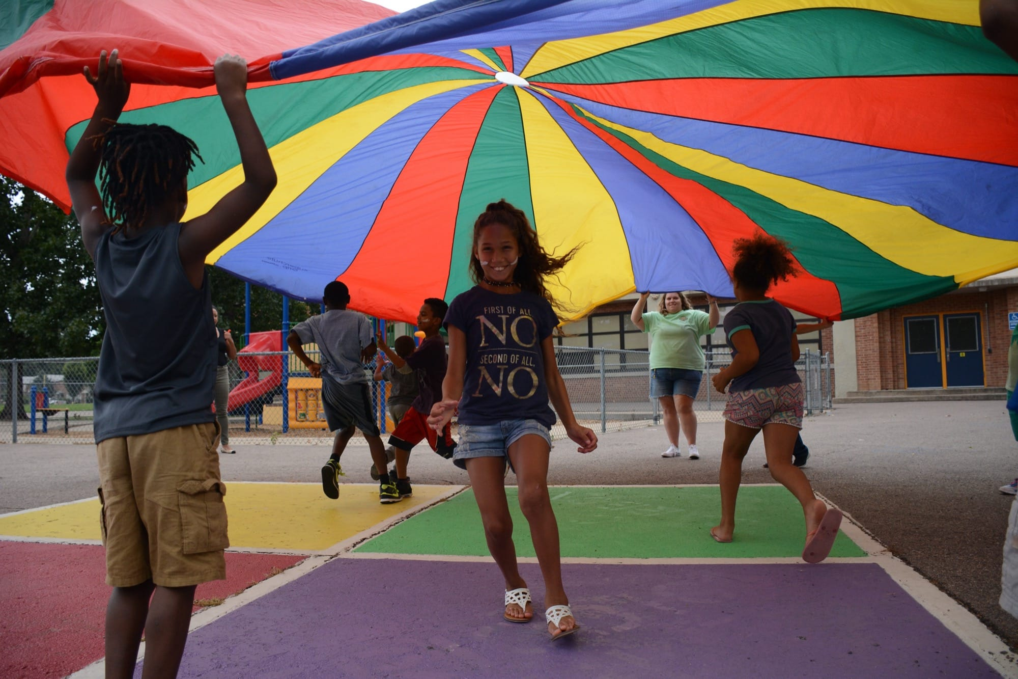 Student smiling at the camera, standing underneath a large rainbow parachute held up by other students