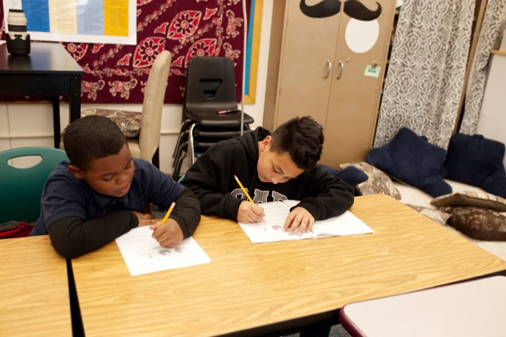 Two students sitting at a table writing in school workbooks
