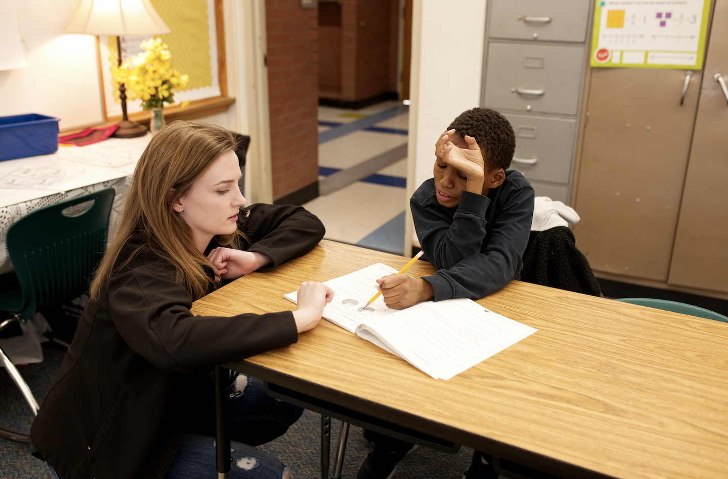 Volunteer kneeling by a student pointing at a workbook problem