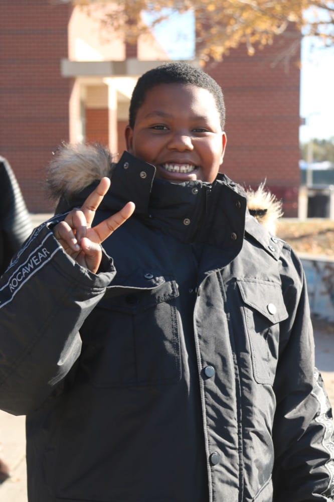 Happy teen making a peace sign at the camera
