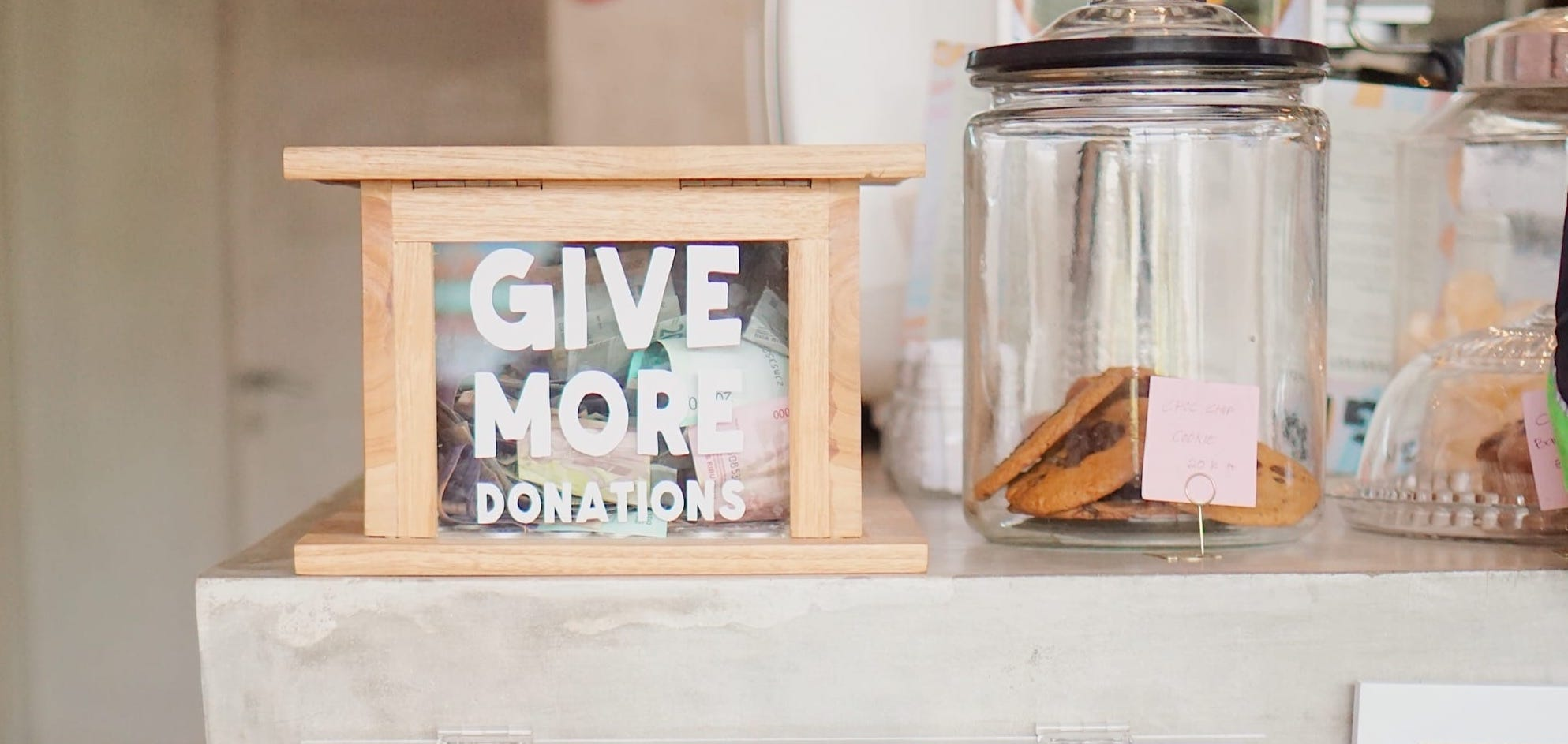 "A wooden donation box that has ""Give More Donations"" written in white lettering, sitting on a counter"