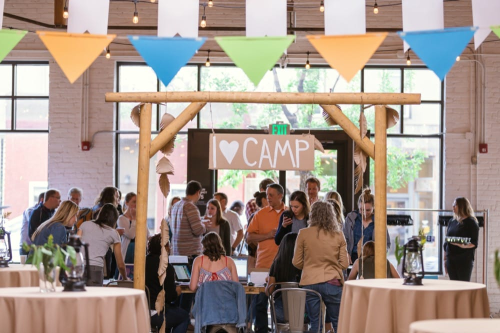People gathering at a Heart & Hand camp event behind a wooden arch and sign