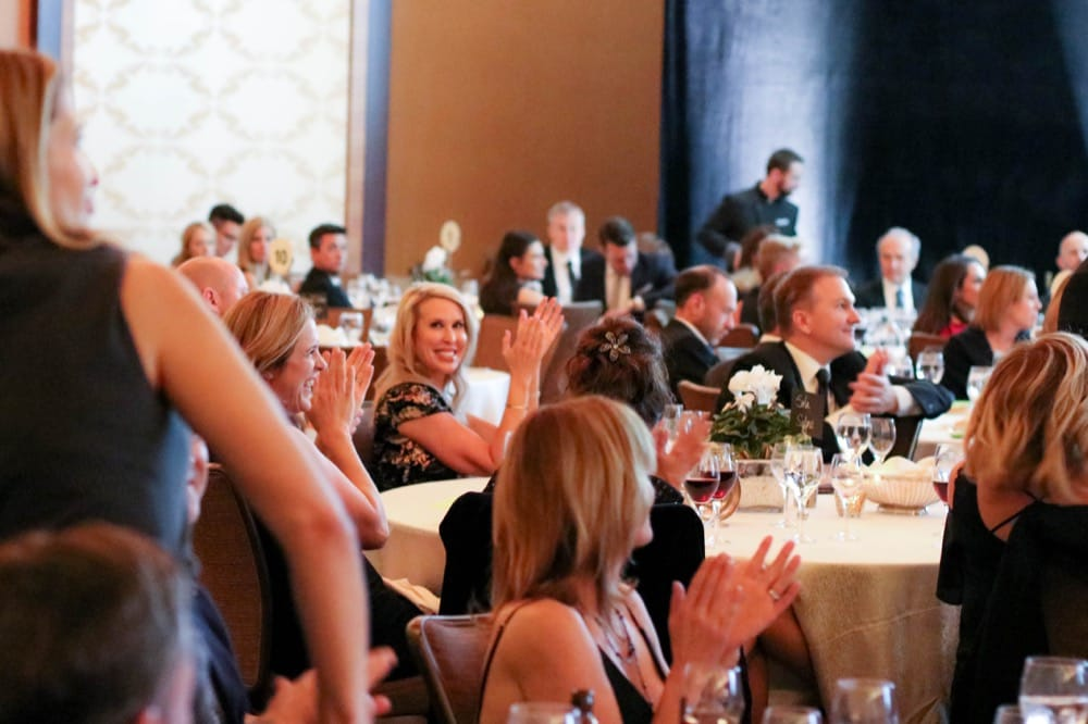 People sitting at tables at a banquet event, smiling and applauding