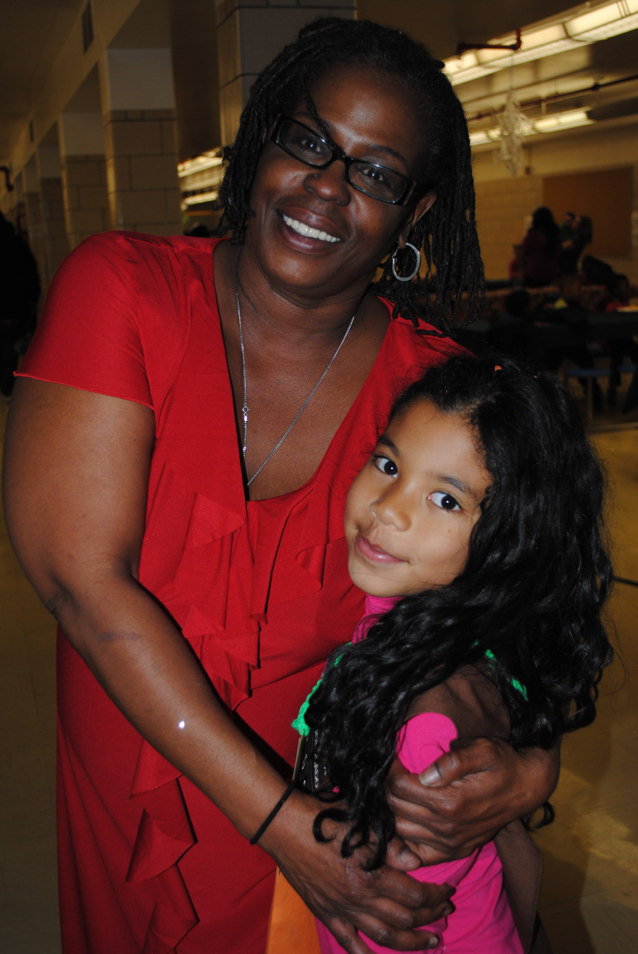 A woman with her arms around a girl, both smiling at the camera