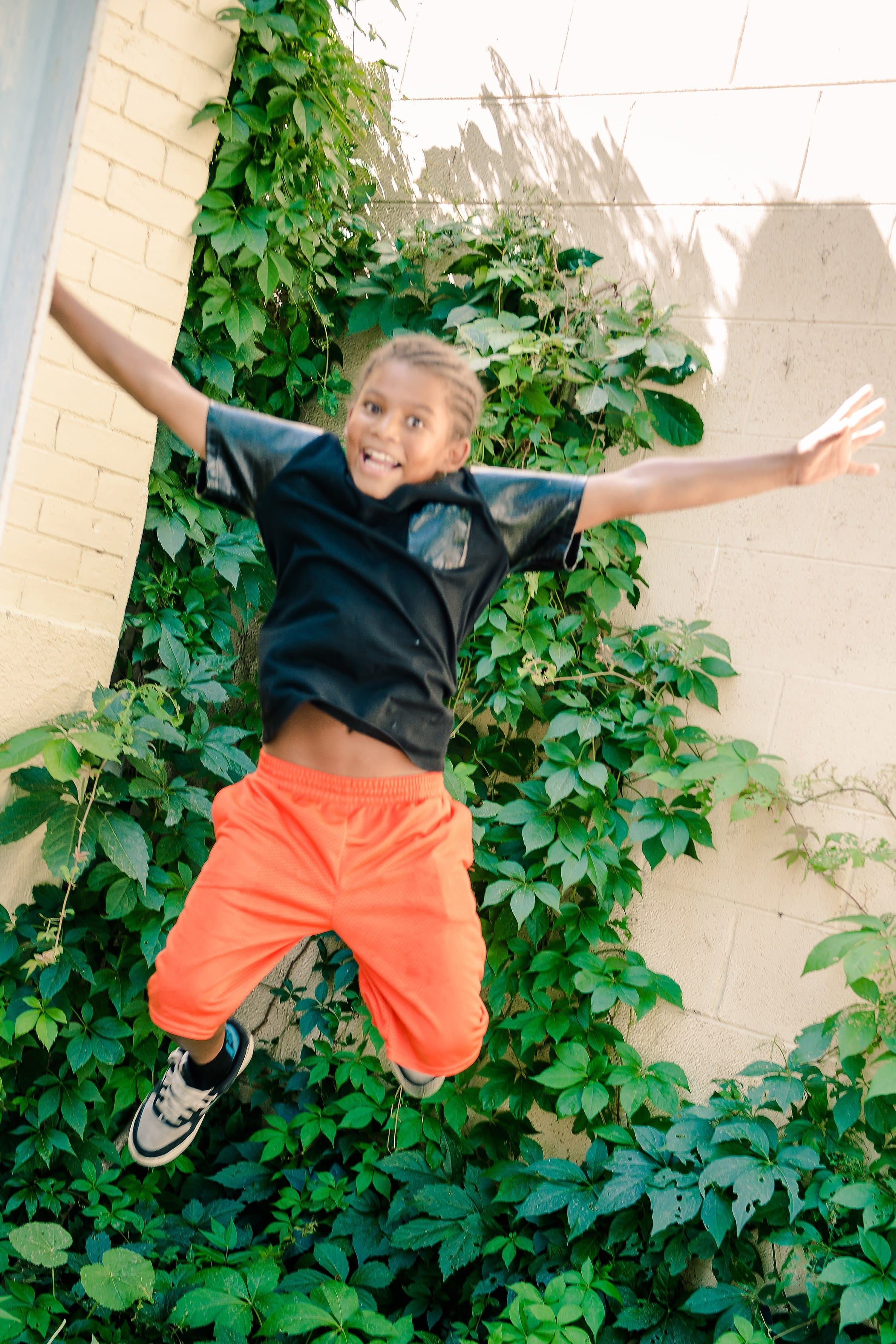 Kid happily jumping in the air in front of green plants growing on a brick wall