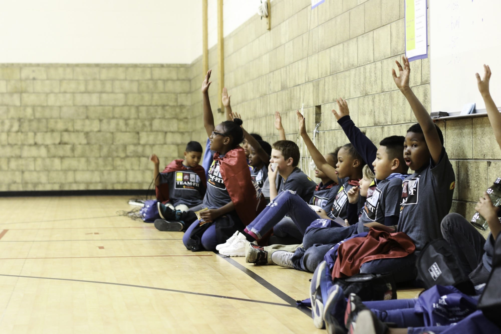 Students sitting again the wall on the floor of a gymnasium, raising their hands excitedly