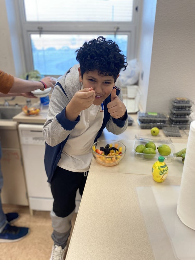 Student eating food, giving a thumbs-up to the camera