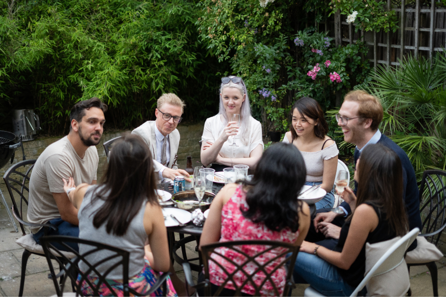 group of friends sitting at the table during the garden party
