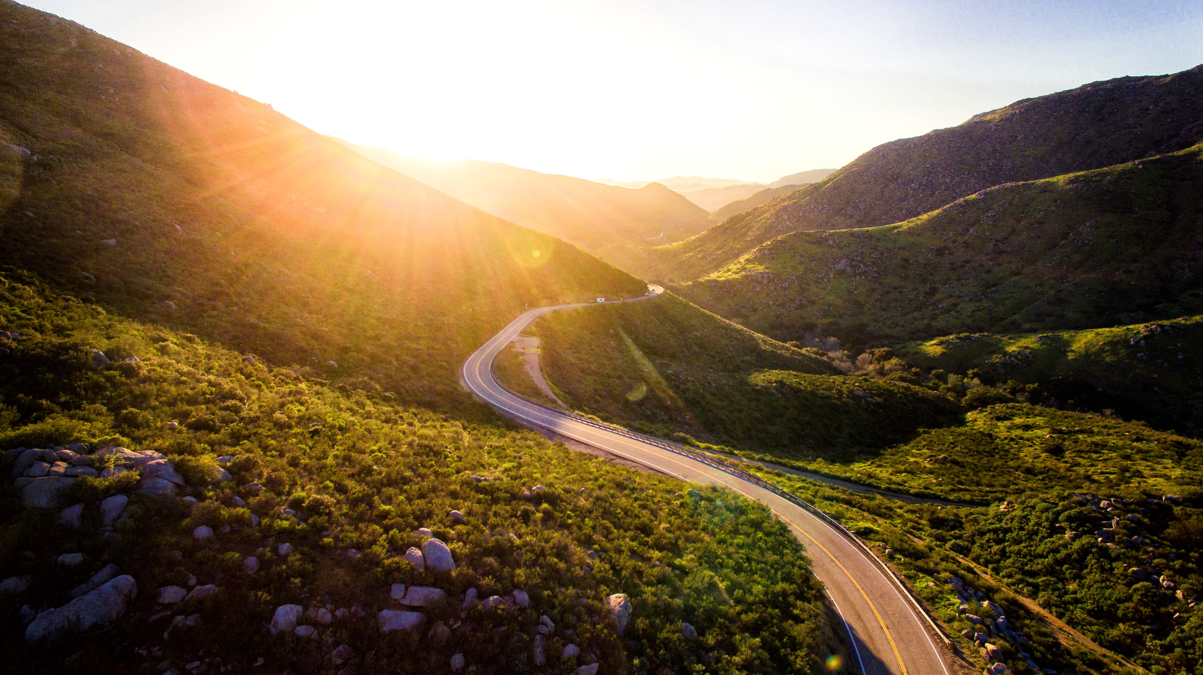 a road cutting through a mountain landscape with a sunrise shining through one of the mountain tops