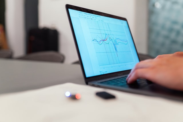 closeup of hands typing on a laptop with line graph on the screen