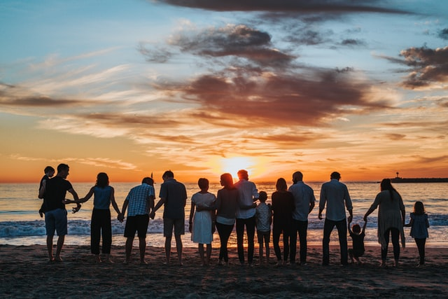 a family standing in front of an ocean shore holding hands and looking at sunset in the distance
