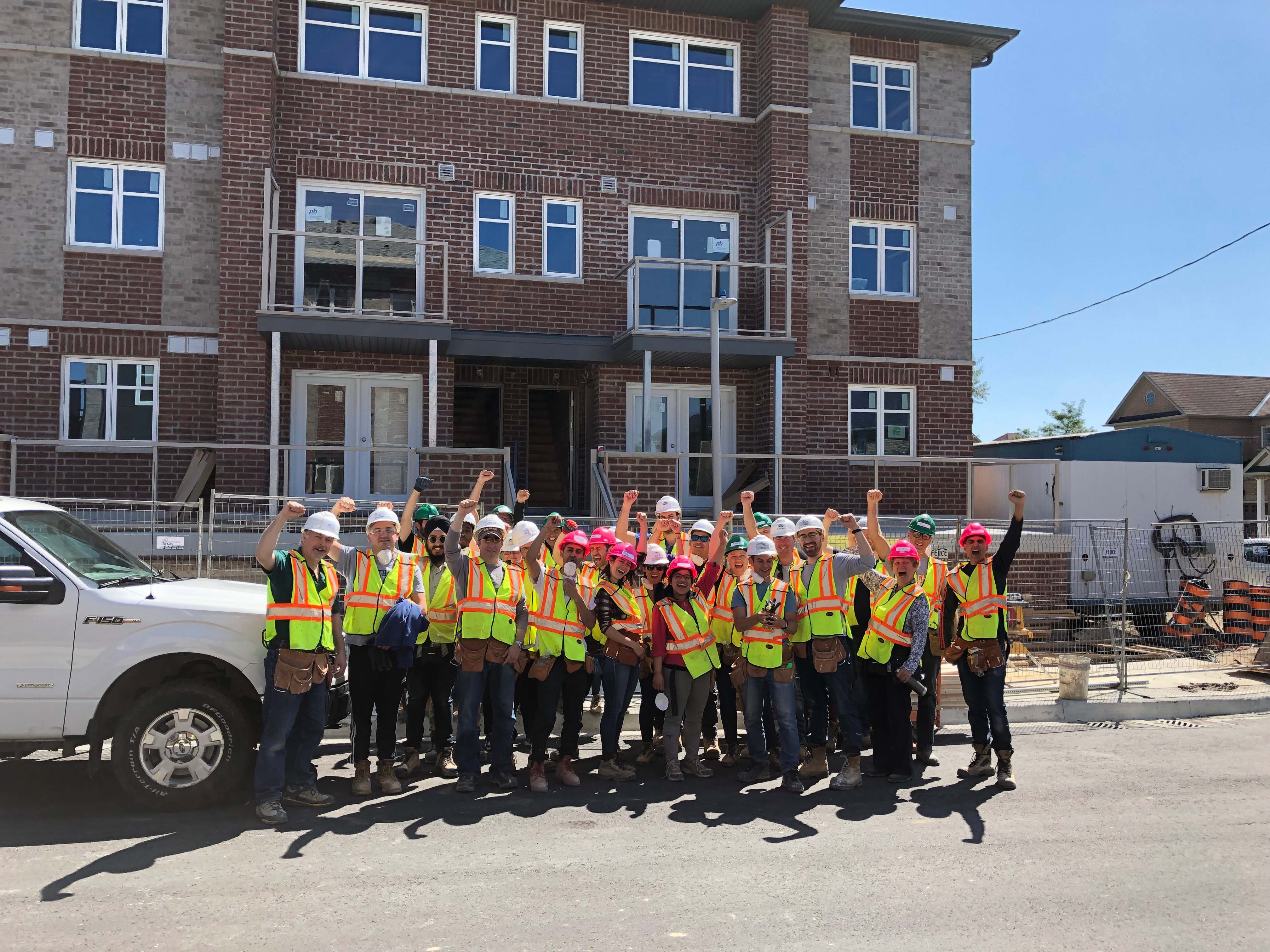 Prime Quadrant team members posing at a volunteering event wearing construction gear
