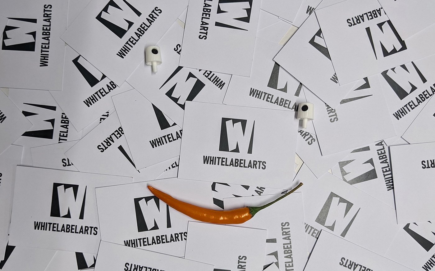 Witte visitekaartjes WhiteLabelArts als achtergrond met 2 NY caps en een oranje chili peper