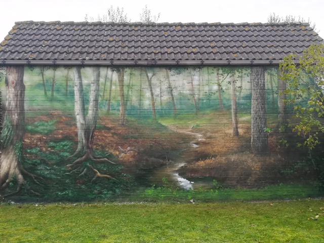 Muurschilderij van een bospad met een libel als detail